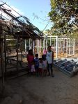Lilibeth with her family posing between her old damaged home which tilted dangerously during the storm, and the new structure being built.