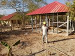 Tatay Pedro poses with his unfinished home, with the Health Center at the background. His old home used to stand to his right.