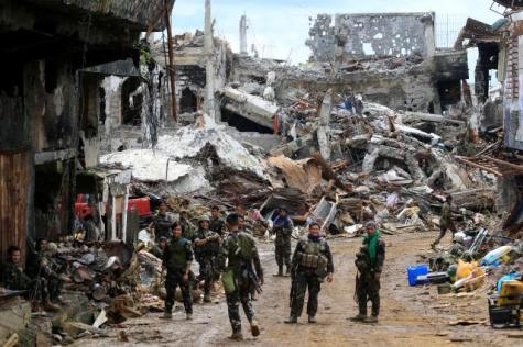 Government soldiers stand in front of damaged houses and buildings in Marawi city