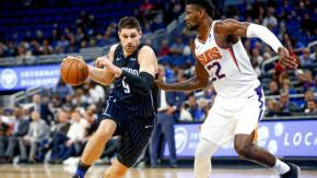 Nikola Vucevic drives past DeAndre Ayton. (USA TODAY Sports)